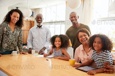 Portrait Of Grandparents Sitting At Table With Grandchildren Playing Games On Family Visit