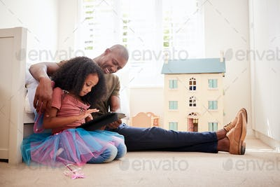 Father With Daughter Sitting On Bed In Childs Bedroom Using Digital Tablet Together