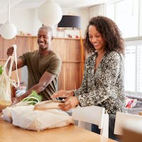 Couple Returning Home From Shopping Trip Unpacking Plastic Free Grocery Bags