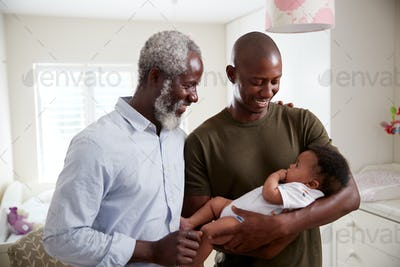 Proud Grandfather With Adult Son Cuddling Baby Grandson In Nursery At Home