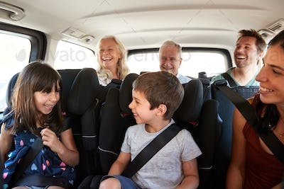 Three generation white family sitting in two rows of passenger seats in a car, looking at each other