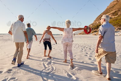 Rear View Of Senior Friends Walking Along Sandy Beach On Summer Group Vacation