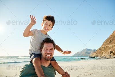 Mid adult white man on a beach, his four year old son sitting on his shoulders waving, close up