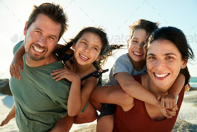 Mid adult white parents piggybacking their kids on a beach, smiling to camera, close up, backlit