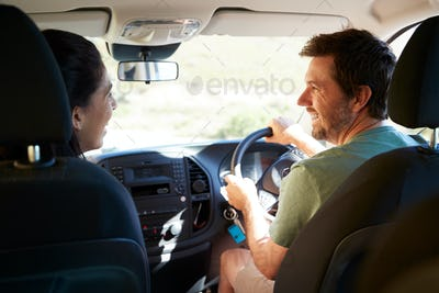 Mid adult white couple driving in their car smiling at each other, back view, close up