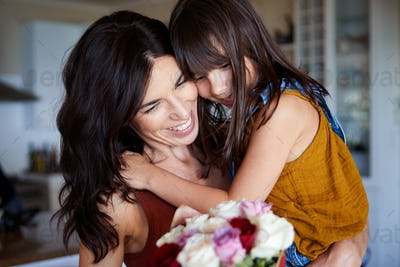 Young white girl giving her mother flowers as a gift on Mother's Day, close up