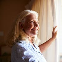 Smiling senior white woman opening the curtains on a sunny morning, side view, close up