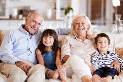 White senior couple and their grandchildren sitting on a sofa together at home smiling to camera