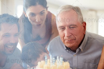 Senior white man celebrating with his family blowing out the candles on birthday cake, close up