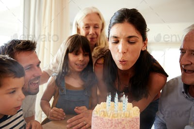 Mid adult white woman blowing out candles on birthday cake watched by her family, close up