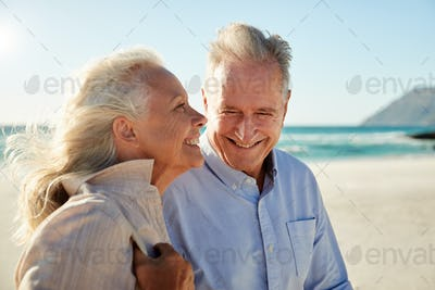 Senior white couple walking on a sunny beach, waist up, side view, close up