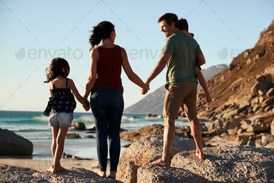 Mid adult parents and their two pre-teen children standing on beach admiring the view, full length