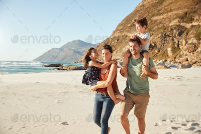 Mid adult white couple walking along on a beach carrying their children during a family holiday