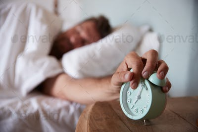Mid adult man asleep in bed, reaching out to alarm clock on the bedside table in the foreground