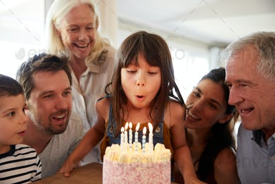 Six year old white girl celebrating her birthday with family blowing out the candles on her cake
