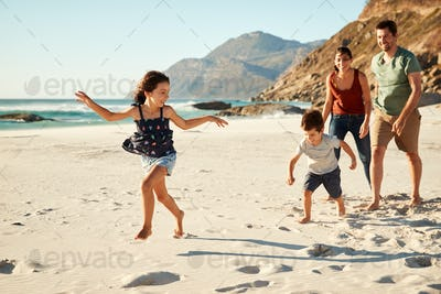Happy young white family on holiday exploring a beach together, full length