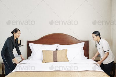 Staff of the hotel making the bed