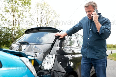 Mature Male Motorist Involved In Car Accident Calling Insurance Company Or Recovery Service