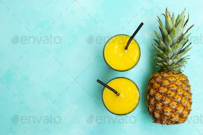 Pineapple with Tropical Fresh Juice, Smoothie on Blue Background. Copy Space. Top View