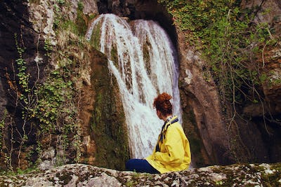 Young woman alone in front of a waterfall