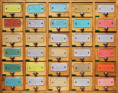 Vintage wooden cabinet with multicolor labels