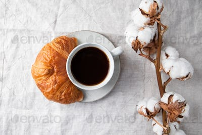 Cup of black coffee with croissant on  table