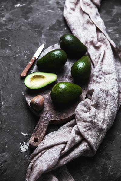 avocado on a cutting board with a kitchen towel in a vintage style
