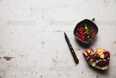 Food photo of red ripe pomegranate pieces in bowl on the table with copy space. Healthy food