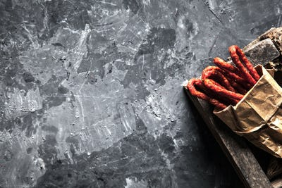 Sausages on a paper texture on a dark background with pepper