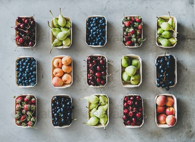 Flat-lay of fresh fruits and berries over grey concrete background