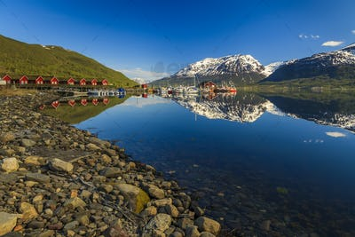 Cottage houses near the sea on a background of blue sky. Norway.
