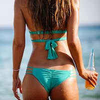 Sexy woman with cocktail enjoying summer vacation on beach