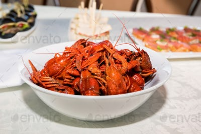 Cooked crayfishes in white plate on table