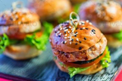 Tasty homemade mini-hamburgers on wooden board close