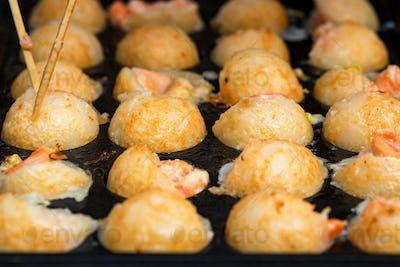 Close up baking prawns in baking pan with holes