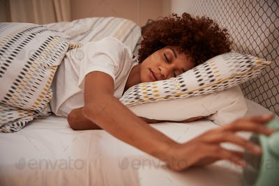 Millennial African American woman half asleep in bed, reaching out for the alarm clock, close up