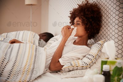 Millennial African American woman sitting up in bed blowing her nose