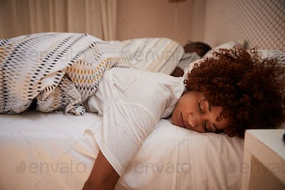 Millennial African American woman lying on her front asleep in bed, her partner in the background