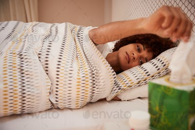 Millennial African American woman lying ill in bed, taking a tissue from a box, side view, close up