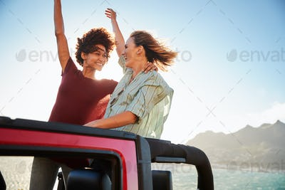 Two millennial female friends on a road trip standing in the back of an open top car, close up