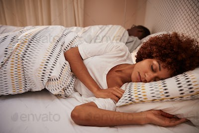 Millennial African American woman lying on her side asleep in bed, her partner in the background