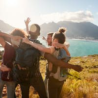 Young adult friends on a hike celebrate reaching a summit near the coast together
