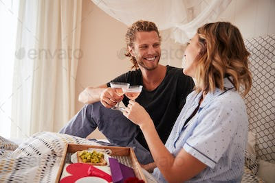 Millennial white couple celebrating, making a toast with champagne in bed, close up