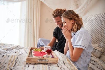 Millennial white man surprising his female partner with breakfast and gifts in bed, close up