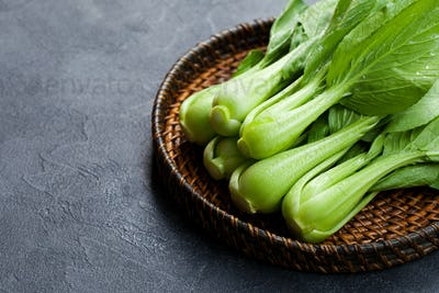 Bok Choy Fresh Salad on Wooden plate. Grey background. Copy Space