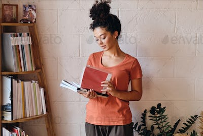 Young gorgeous woman with dark curly hair in T-shirt holding books in hands standing near bookshelf