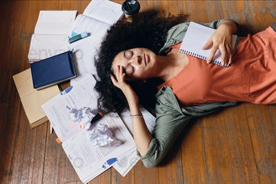 Young attractive smiling student girl with dark curly hair lying on floor with textbooks around