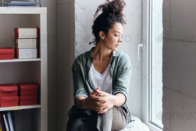 Pensive woman sitting on window sill in audience of university and thoughtfully looking aside