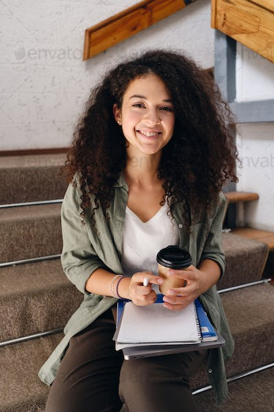 Young joyful woman sitting on stairs in university with coffee in hand happily looking in camera