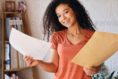 Young cheerful woman in T-shirt joyfully looking in camera holding letter with exam results in hands